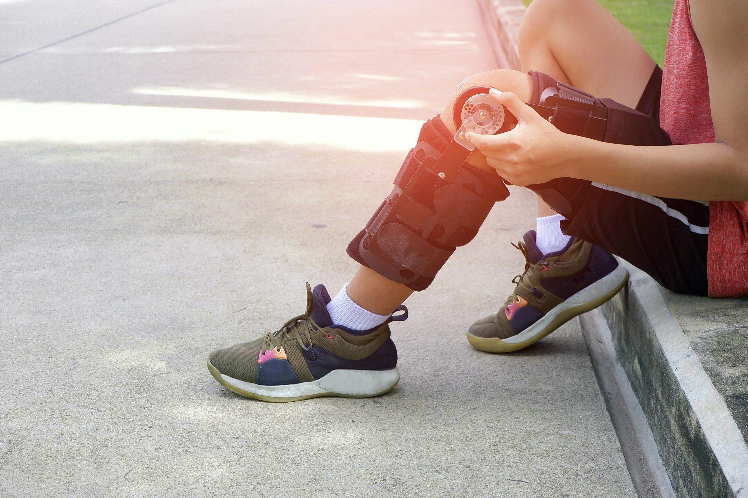Teenage boy sitting on sidewalk with knee brace